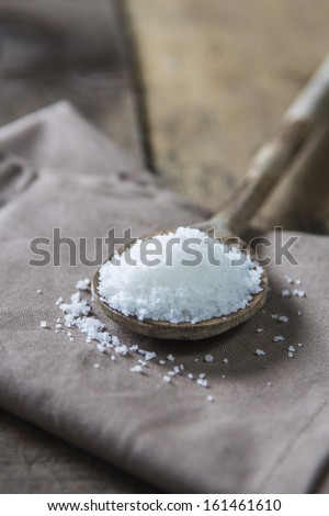 Sea Salt Fleur de Sel on wooden spoon on rustic wooden background - stock photo