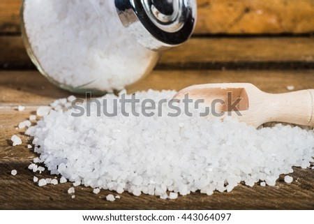 Sea salt in a jar on a wooden background