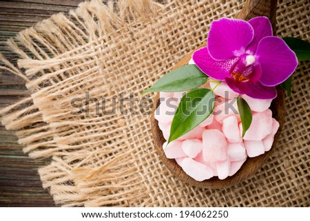 Sea salt in a spoon with a wooden background and  pink orchid.