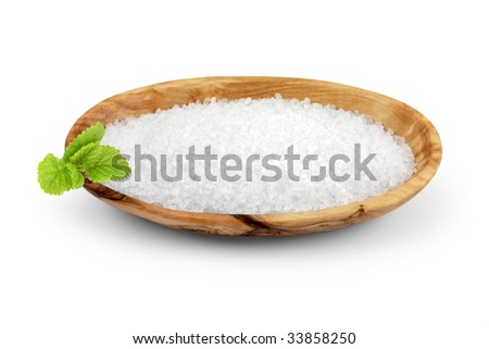 Sea salt in an olive wood oval bowl with lemon balm herb leaf sprig, over white background.
