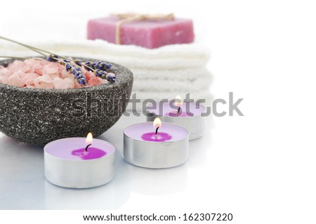 Sea salt in stone bowl with candles and herbal soap isolated on a white background with reflection - stock photo