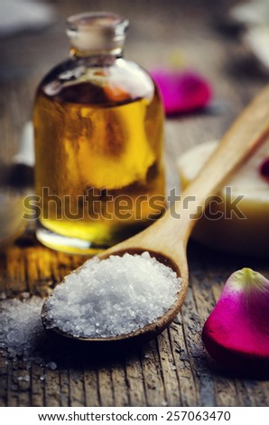 Sea salt in wooden spoon and aromatic oil. Vintage effect. - stock photo
