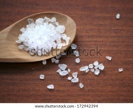 Sea salt in wooden spoon on a table - stock photo