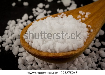 Sea salt In wooden spoon on dark stone background - stock photo