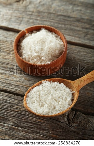 Sea salt in wooden spoon on grey wooden background