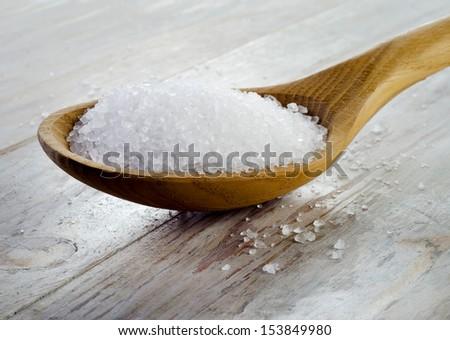 Sea salt in  wooden spoon.Selective focus - stock photo