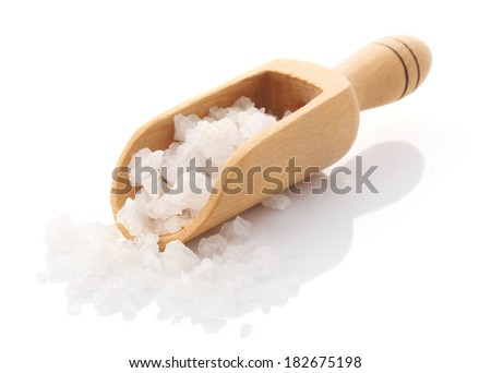 Sea salt poured from wooden scoop isolated on white background  - stock photo