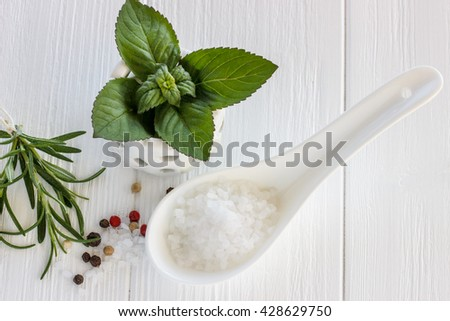 Sea salt scented herb rosemary and mint leaves on wooden background