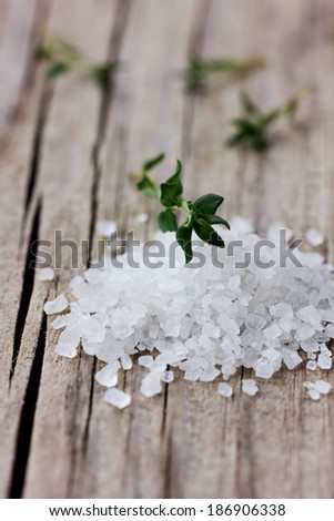 Sea salt with a fresh herbs thyme on a wooden rustic surface - stock photo