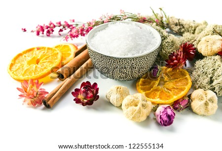 Sea salt with dried fruits, plants and flowers on white background - stock photo