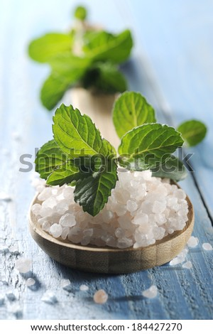 sea salt with mint on a blue wooden table - stock photo