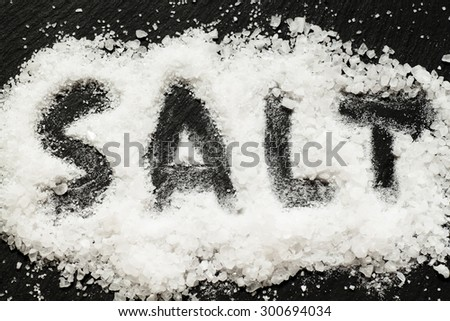 "Sea salt with the inscription ""salt"" on a dark background, selective focus - stock photo"