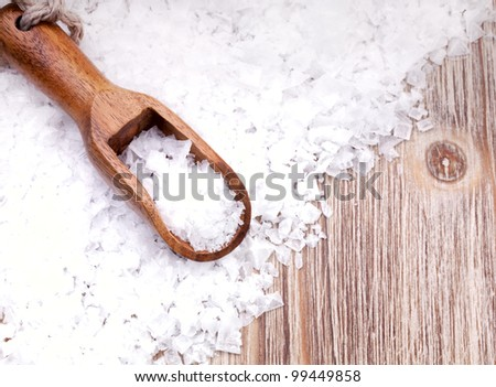 Sea salt with wooden scoop on vintage  surface - stock photo