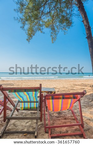 Sea sand sky and vintage summer day. Foot print on a summer sandy ocean beach. Lounge chair in the tropical beach. Close up sand with blurred sea sky background, summer day, copy space for product.