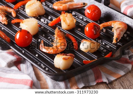 Sea scallops and shrimp are fried on a grill pan close-up. Horizontal - stock photo