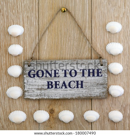 Sea shell and gone to the beach sign over old oak background. - stock photo