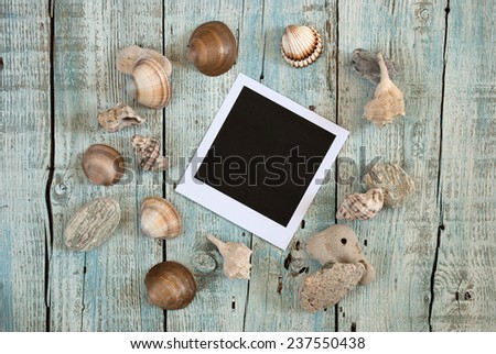 Sea shells and instant photo frame on old wooden table - stock photo