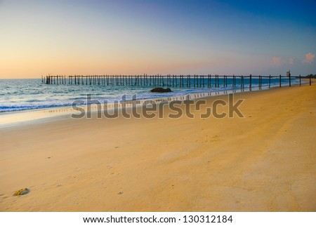 Sea shore and old bridge in sunset time - stock photo