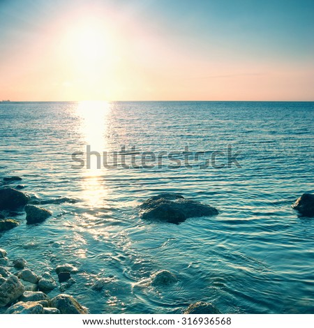 Sea shore and stones at sunset. Seascape with shining sun - stock photo