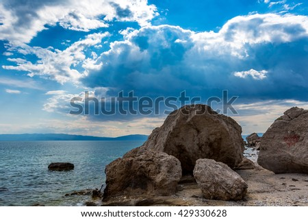 Sea shore with big rocks in Greece A beautiful seascape of the blue sea in Greece with sun reflections, big white clouds, sun rays, sand, sea shells - stock photo