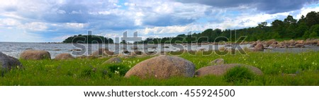 Sea shore with huge erratic boulders and lush green meadow - stock photo