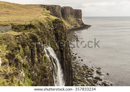 Sea shoreline with Mealtfalls in foreground and Kilt Rock in the background, Skye Island, Scotland - stock photo