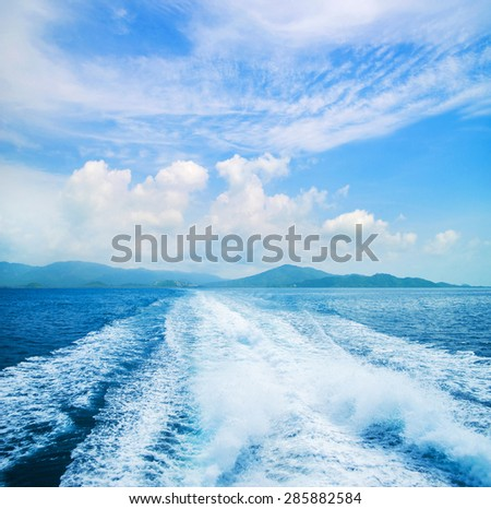 Sea, sky and a trace on the water. - stock photo