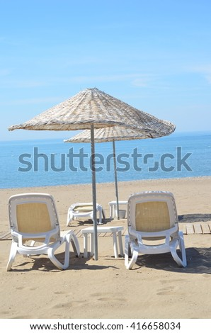 Sea, sky, beach with beach chairs and umbrella