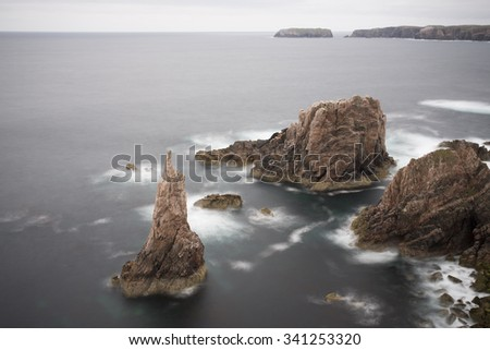 sea stacks in a bay on the coast of scotland with incoming tide - stock photo