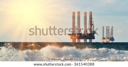 Sea station of gas production. Drilling platforms in the sea at sunrise against a blue sky - stock photo