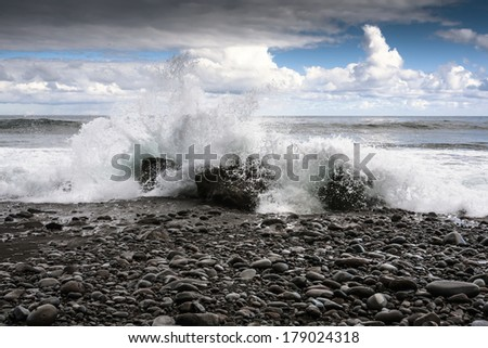 Sea, Stones and Splashing Waves Photo with Clouds on Background