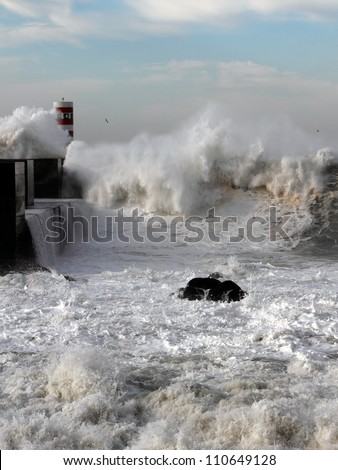 Sea storm with waves crashing against the pier at the mouth of the Douro River on a sunny day; Focus on the 1st plane/foreground - stock photo