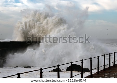 Sea storm with waves crashing against the pier at the mouth of the Douro River on a sunny day - stock photo