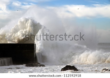 Sea storm with waves crashing against the pier at the mouth of the Douro River on a sunny day