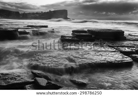 sea stormy sunrise at Avalon beach in Sydney with strong waves hitting mighty rocks and flowing as blurred water over stones in black-white dramatic image - stock photo