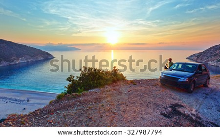Sea sunset view of Myrtos Beach and woman near car (Greece,  Kefalonia, Ionian Sea).