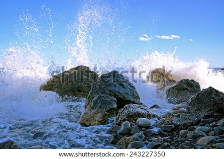 Sea surf with stones and water splashes - stock photo