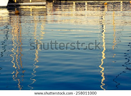 Sea surface in marina - sunlight and reflections on water. Abstract background for your concept of the sea vacation on the yacht. - stock photo