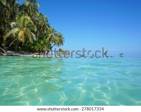 Sea surface with turquoise water and lush tropical island shore with coconut trees, Caribbean, Panama - stock photo