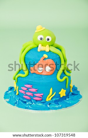 Sea themed birthday party cake with green octopus with hat bow tie and eyes and orange submarine and pink fish on two round blue double tier butter iced cake isolated on a green seamless background