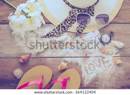 "Sea travel accessories A hat, sunglasses, sandals. Placed on wooden with word 'LOVE"" on sand. - stock photo"