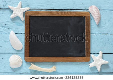 Sea travel frame decor with seashells over wooden background with small blackboard with Copy Space to add your own text - stock photo