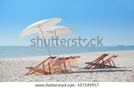 sea, tropical beach with umbrella and chairs