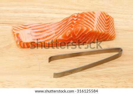 Sea trout fillet with pin boning tweezers on a wooden board - stock photo
