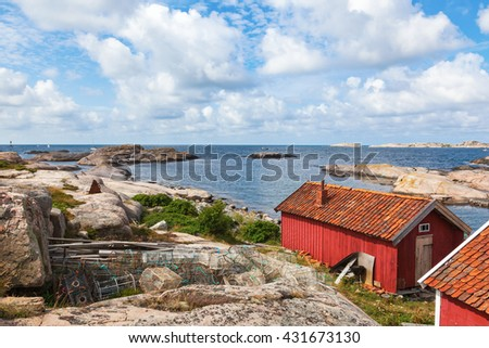 Sea view at a red house with lobster traps - stock photo