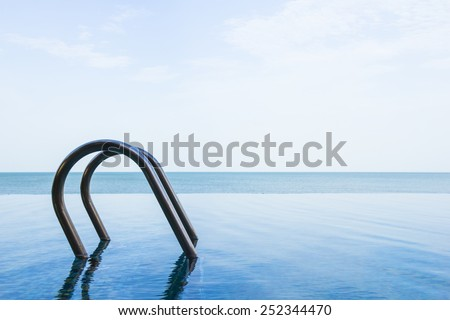 Sea view of infinity swimming pool with sky - stock photo