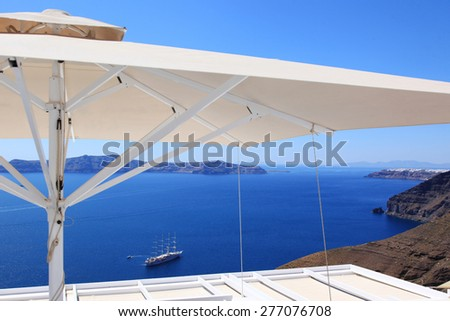 Sea view under umbrella on Santorini island in Greece - stock photo