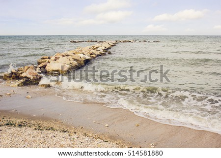Sea view with a long stone pier at the Adriatic Sea shores in Italy