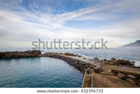 Sea view with long stone pier at the Atlantic ocean shores of Madeira island. Man fishing at this nice weather and calm january evening. Seixal town, Madeira, Portugal.