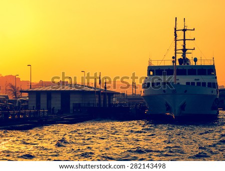 Sea voyage in Golden Horn on the ferryboat. Silhouettes of turkish steamboat,  Stambul harbor at sunset. Old passenger ship, golden sundown in Istanbul. - stock photo